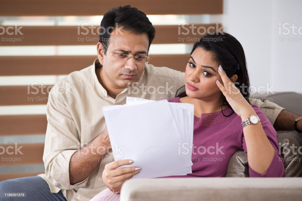 Worried Indian couple with financial bills at home