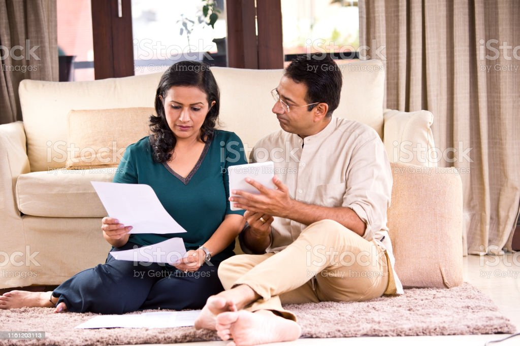 Serious Indian couple with financial bills and digital tablet at home