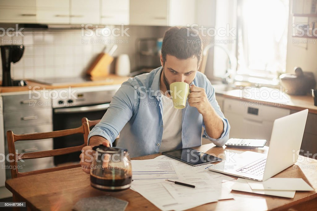 Photo of a man having coffee while doing home budgeting