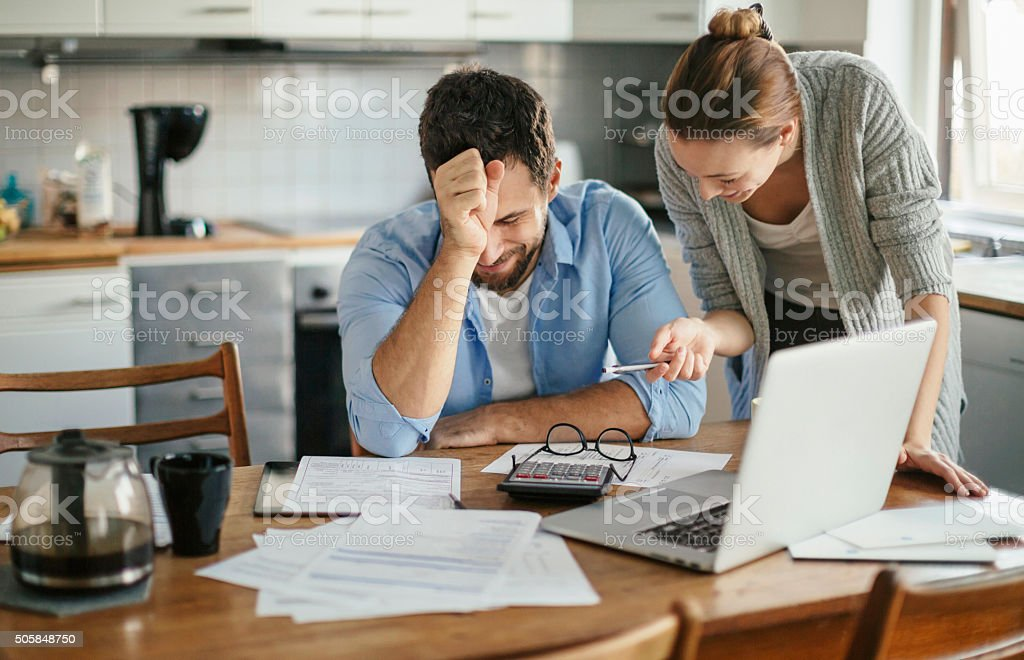 Photo of a young smiling couple calculating home finances