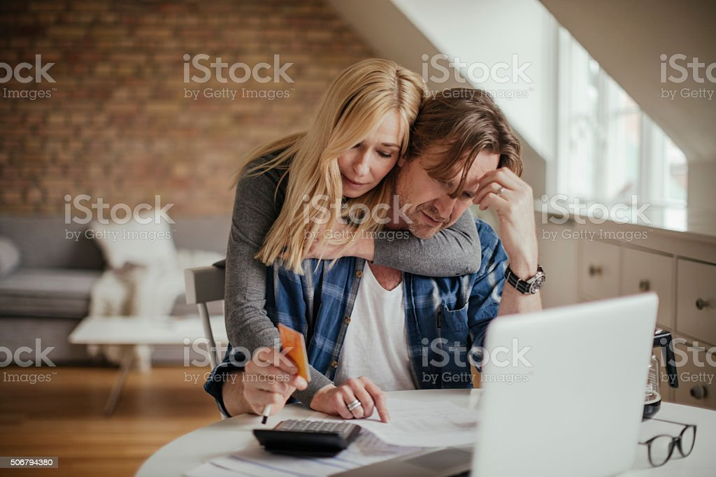 Photo of worried mature couple calculating home finances