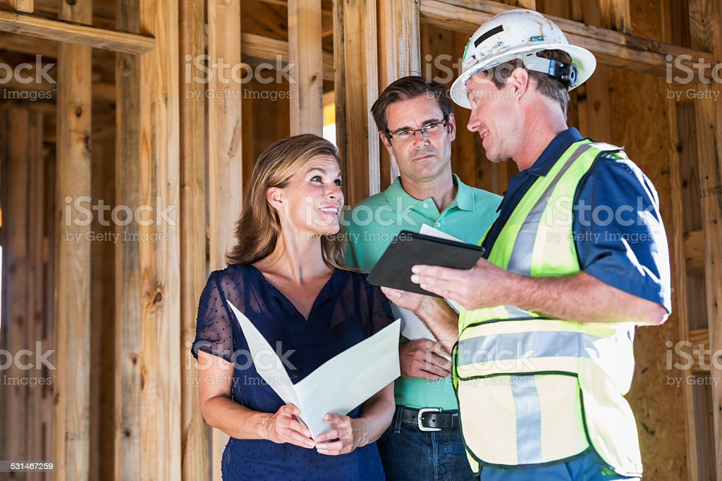 Home builder talking with couple at construction site stock photo