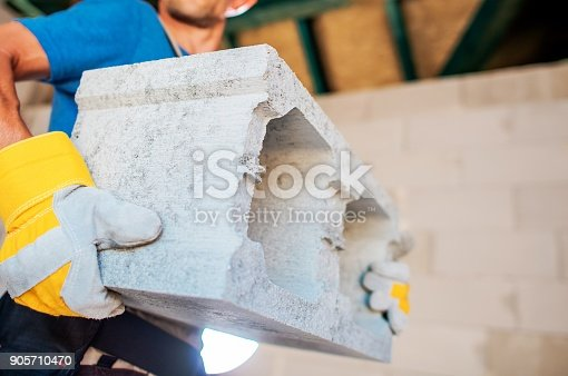Home Builder with the Concrete Block. Caucasian Construction Worker Moving Building Materials.