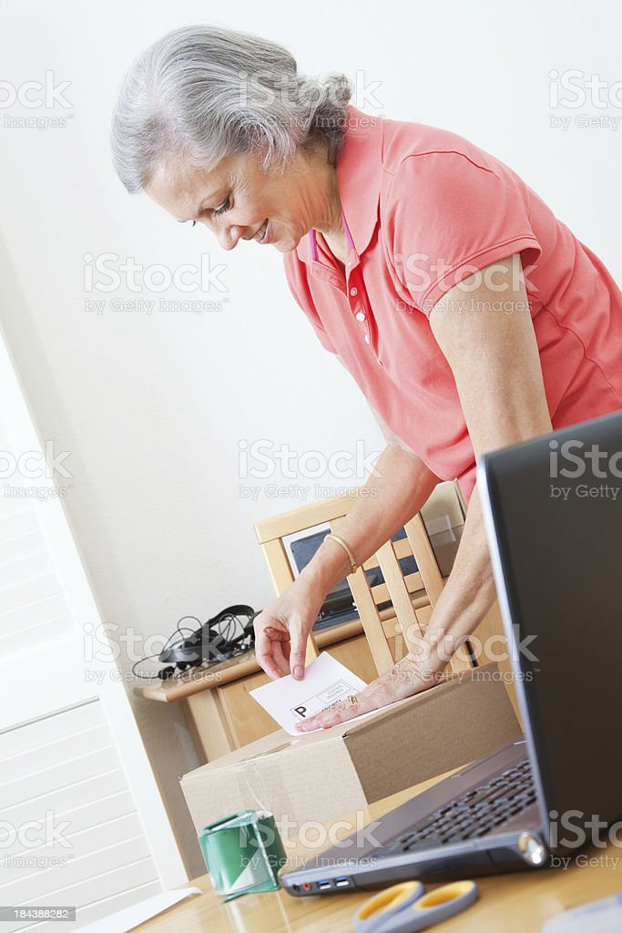 Home Business Woman Putting Shipping Label on Box royalty-free stock photo
