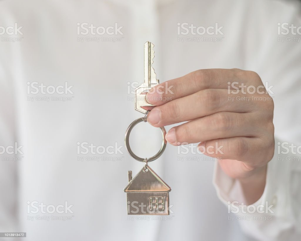 Home buyer insurance concept with house key in broker agent or salesman person's hand giving to customer stock photo