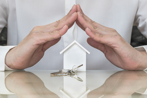 istock Home buyer protection planning concept with house key in insurance broker agent's hand coverage or in salesman person 961634108