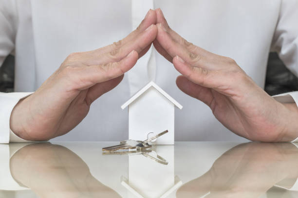 Home buyer protection planning concept with house key in insurance broker agent's hand coverage or in salesman person stock photo
