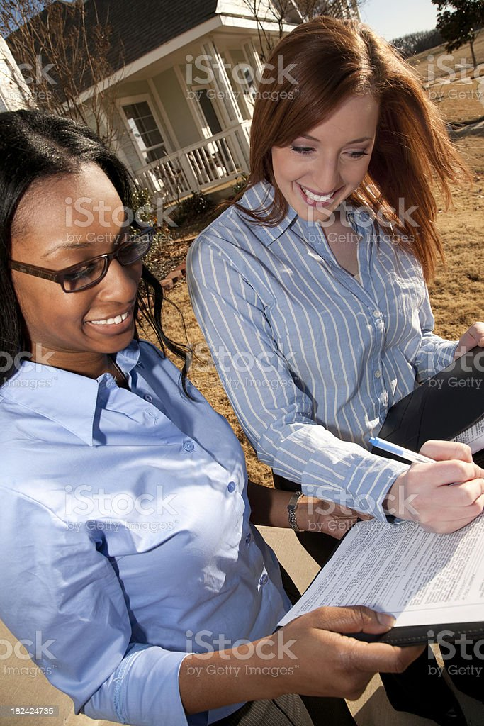 Home Buyer Signing Contract Papers with Realtor Outside Residential House royalty-free stock photo