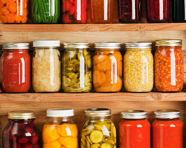 Home Canning Fruit and Vegetable Food Preserves in Storage Shelves stock photo