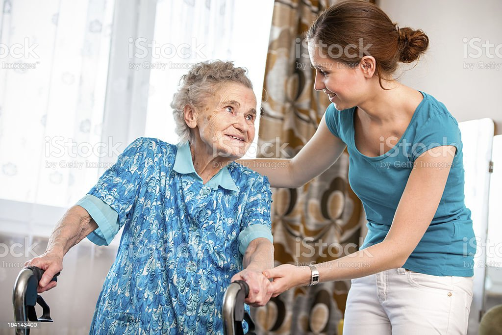 Home care Senior woman with her caregiver at home 80-89 Years Stock Photo