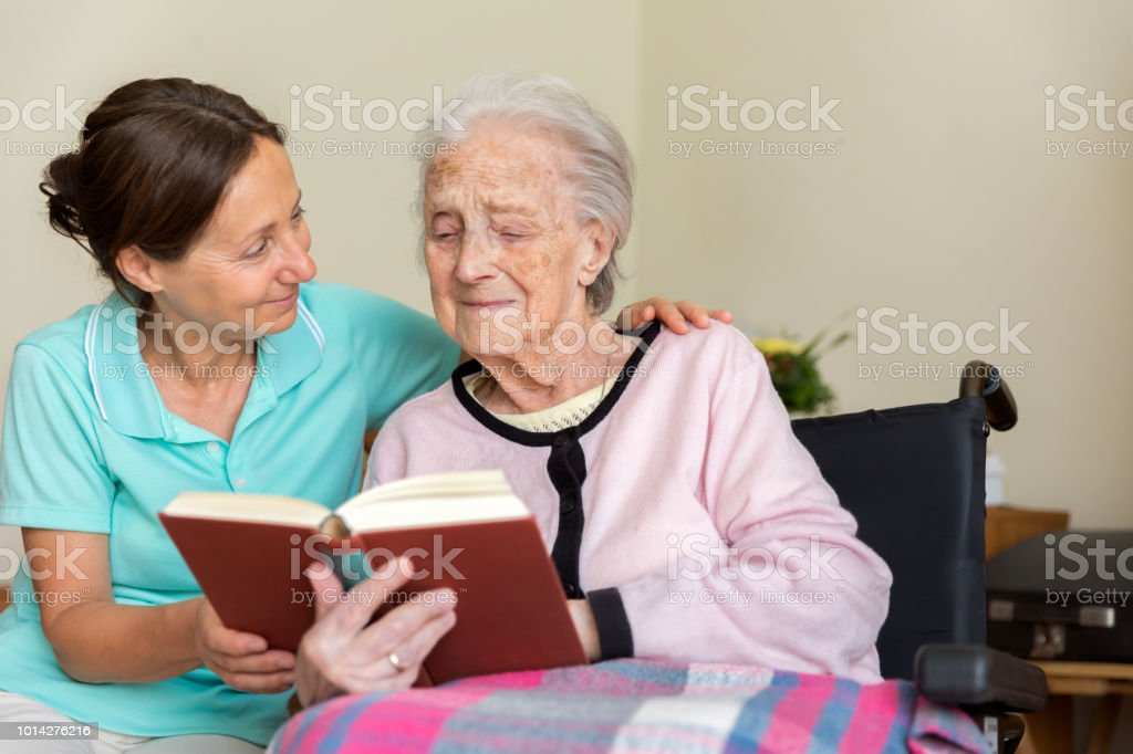 Home caregiver and senior adult woman reading a book