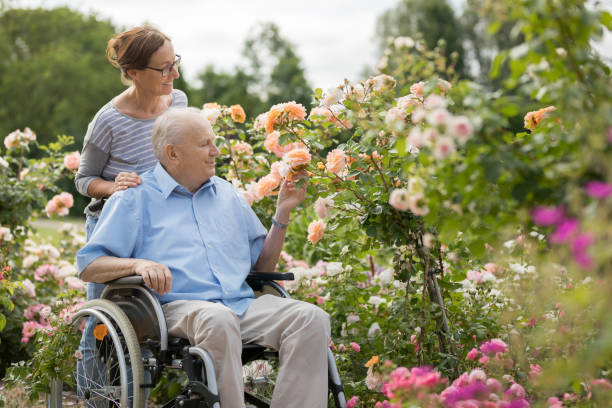 Heimpfleger und Senior im Rollstuhl, zu Fuß im Freien – Foto