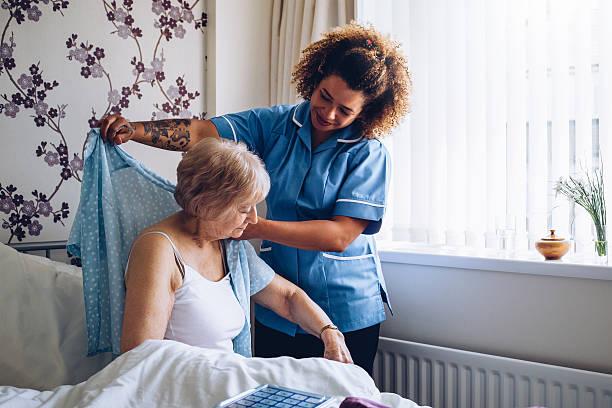 home caregiver dressing senior - raam bezoek stockfoto's en -beelden