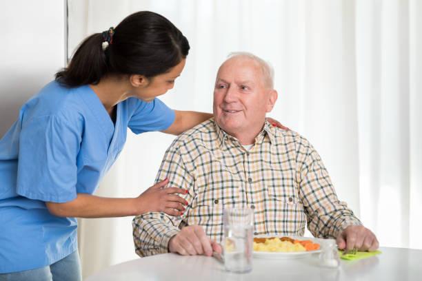 Heimbetreuer geben Seniorenessen – Foto