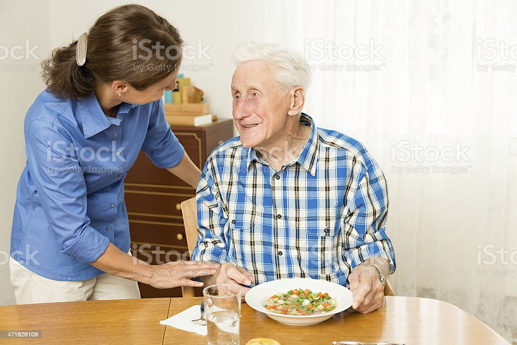 Home caregiver giving senior man lunch stock photo