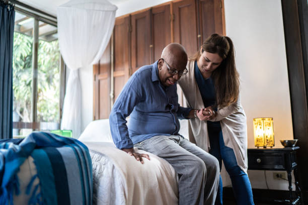 Home caregiver helping a senior man standing up at home stock photo