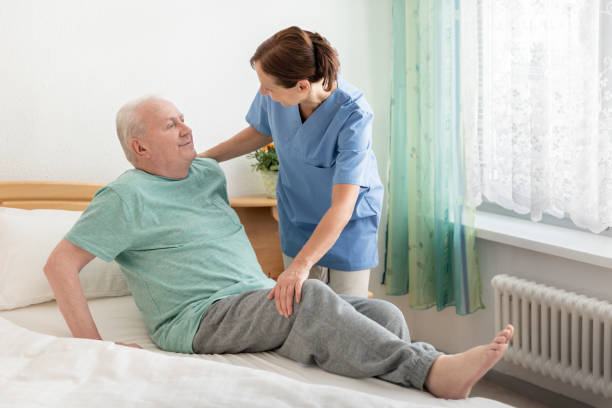 Hauspflegebedürftiger helfen einem älteren Mann aus dem Bett – Foto