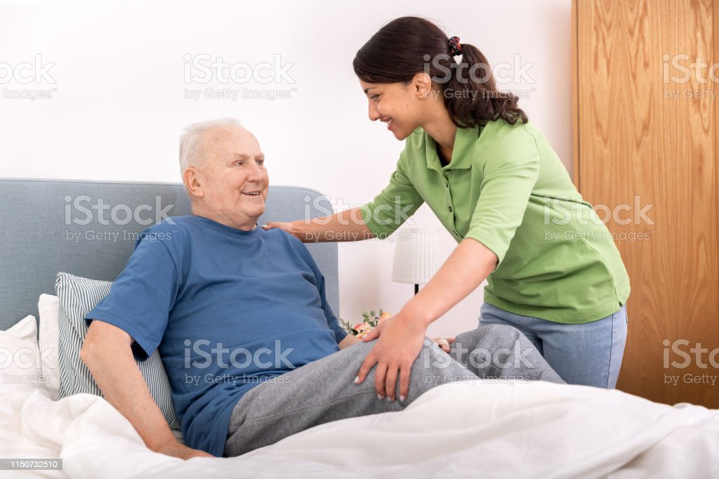 Nursing home – home caregiver helping senior man