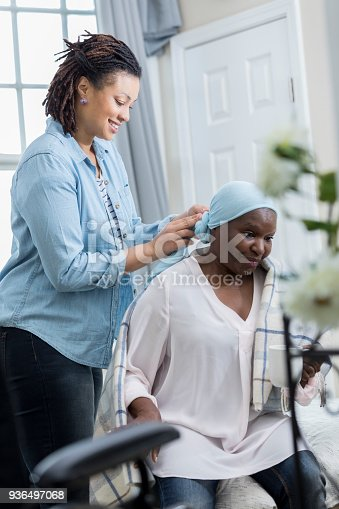 932074776 istock photo Home caregiver helps patient with cap 936497068
