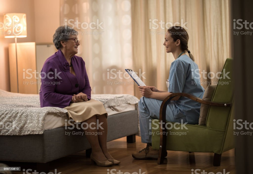 Young nurse sitting and talking with senior women at home