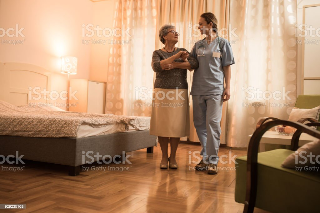 Young home caregiver nurse walking and talking with senior women at...
