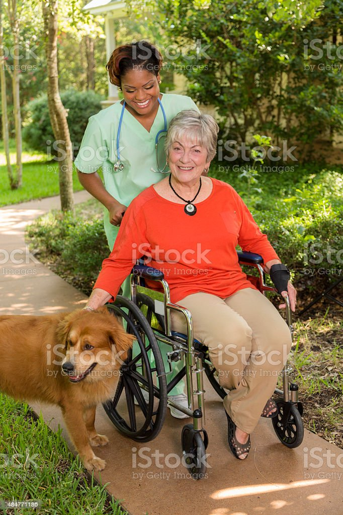 A senior adult woman patient wearing a red shirt and using a...