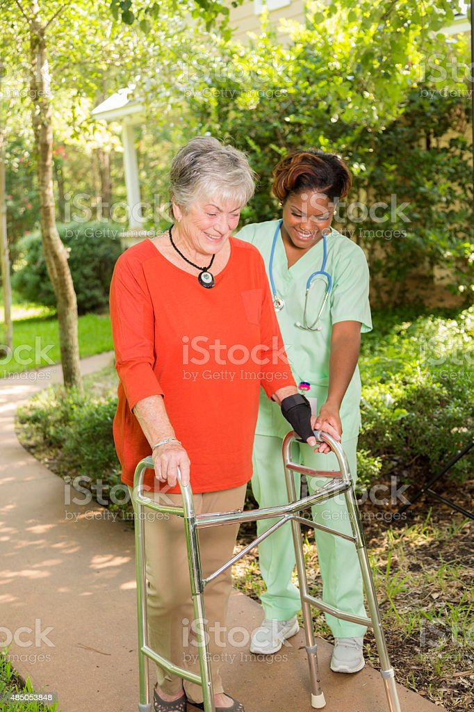 A senior adult woman patient wearing a red shirt and using a walker...