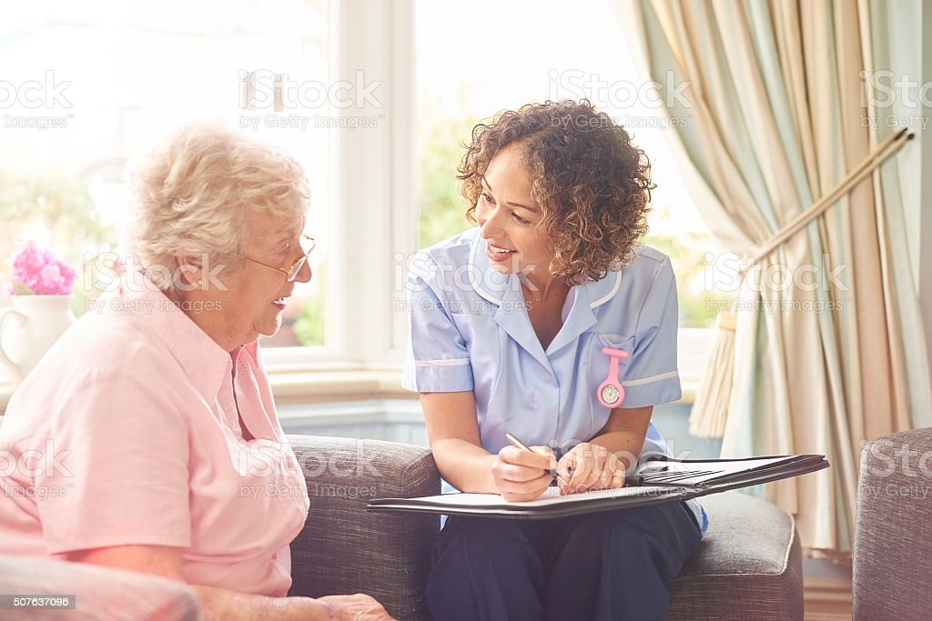 a senior woman in her home chats to her home carer . The nurse is...