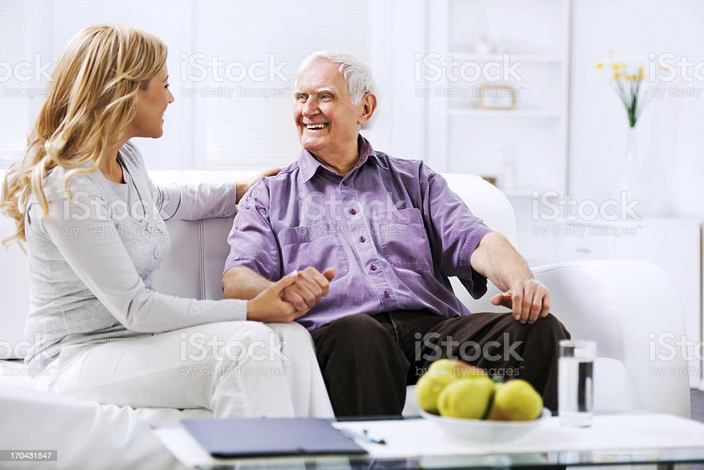 Home caregiver sitting n the sofa with an elderly man stock photo