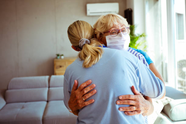 Home caregiver supporting senior woman during coronavirus pandemic stock photo