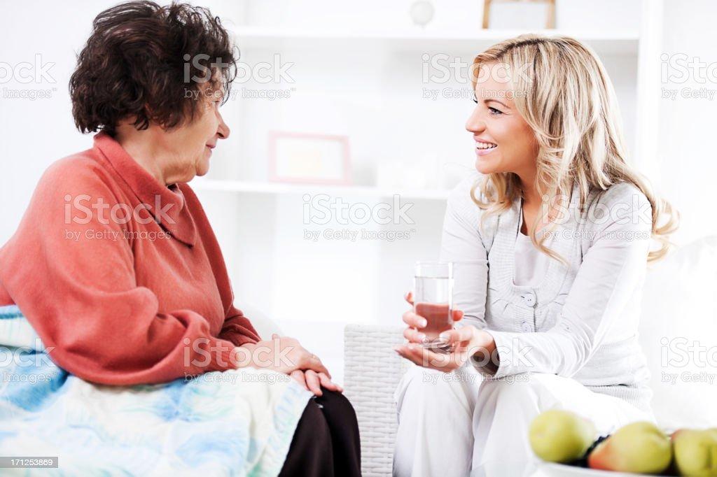 Home caregiver talking to a senior woman. royalty-free stock photo