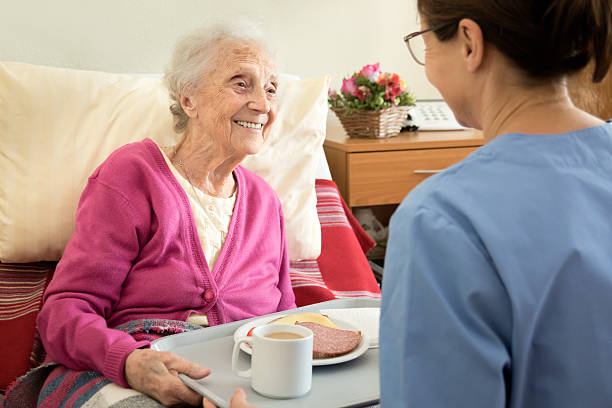 Home caregiver with senior adult woman, serving a meal stock photo