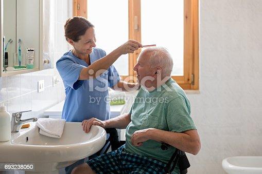 istock Home Caregiver with senior man in bathroom 693238050