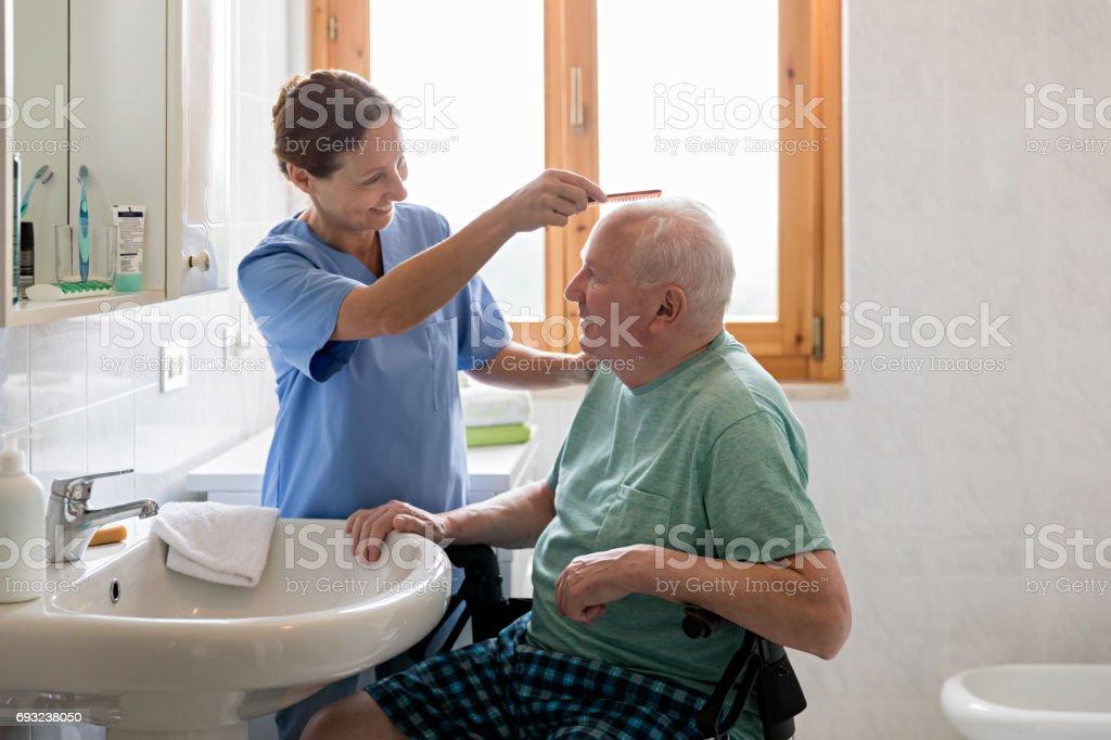 Aide familiale avec homme senior dans salle de bain - Photo