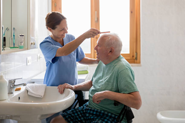Home Caregiver with senior man in bathroom stock photo