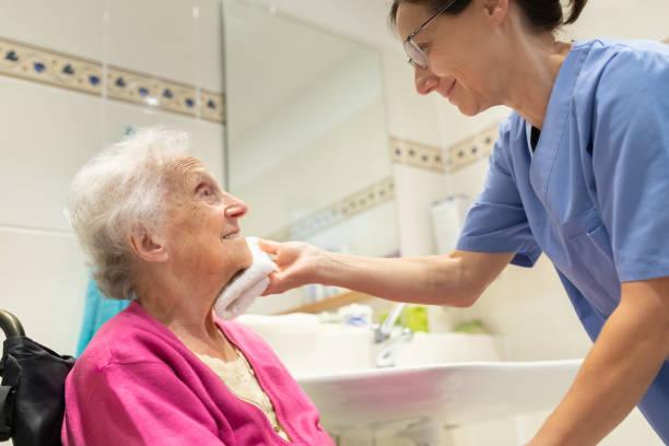 Home Caregiver mit Seniorin im Badezimmer – Foto