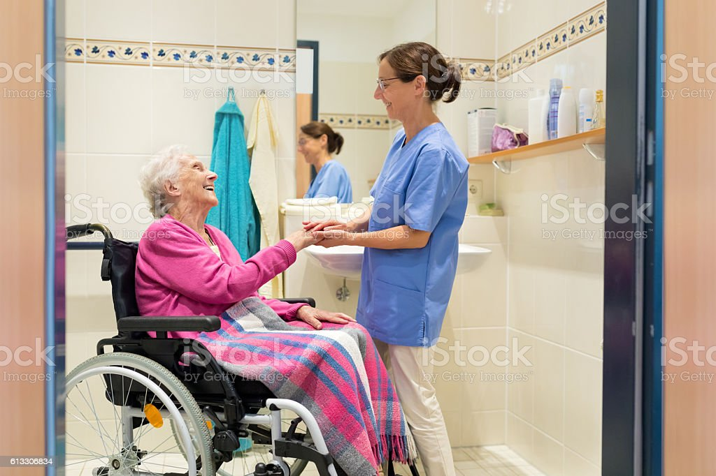 Home Caregiver with senior woman in bathroom, senior woman sitting in...