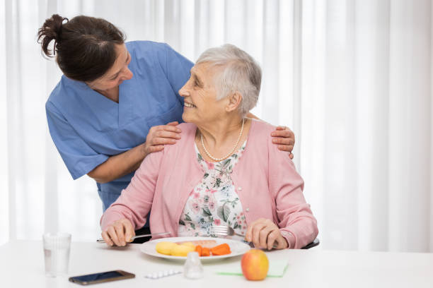 Home caregiver with senior woman, serving a meal stock photo