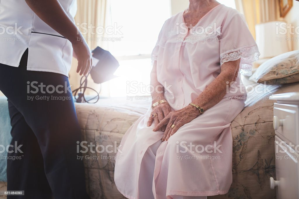 Home caregiver with senior woman sitting on bed stock photo