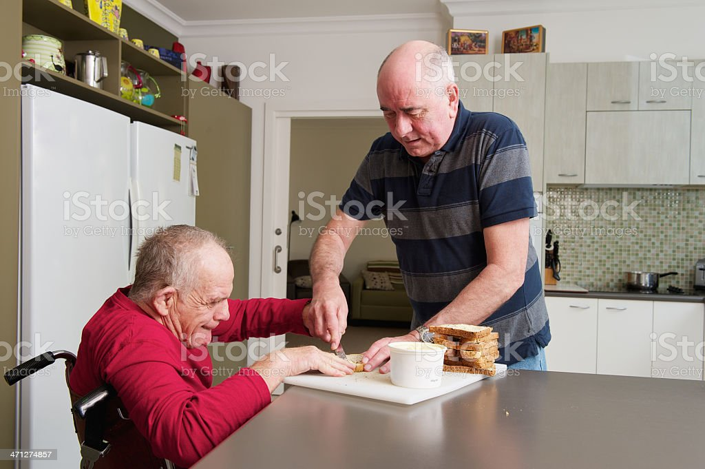 Home Carer assisting Man with a Disability stock photo