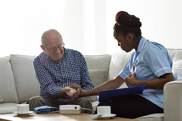 home carer checking patients pulse at home - taking pulse stock photos and pictures