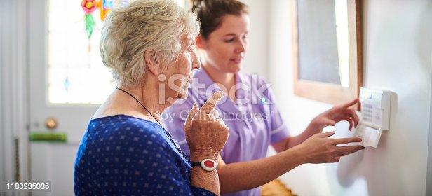 istock home carer showing senior woman her alarm panel 1183235035