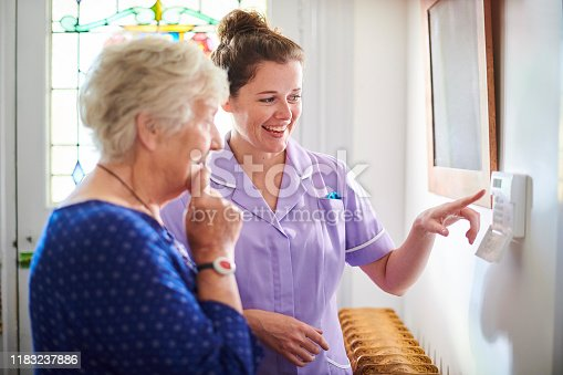 istock home carer showing senior woman her alarm panel 1183237886
