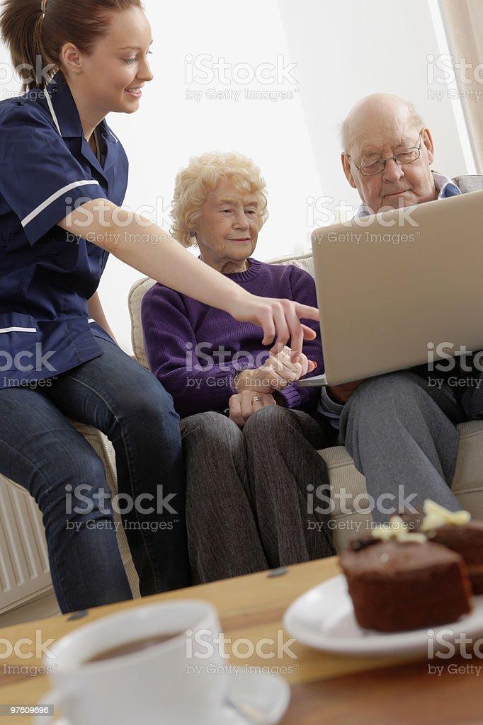 home carer showing something on laptop to senior couple royalty-free stock photo