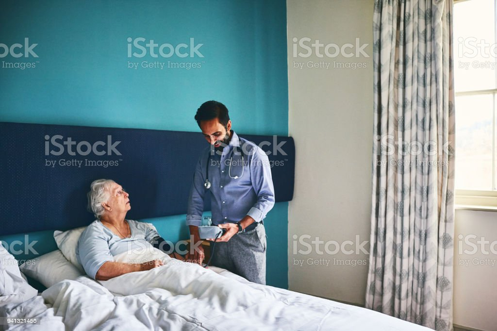 Home carer taking blood pressure of a senior woman at care home stock photo
