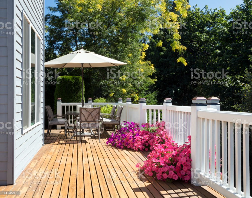 Home cedar deck during bright summer day with blooming garden of flowers stock photo