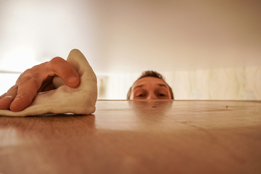 home cleaning concept. a man wipes dust from a high cabinet in his house. focus on hand