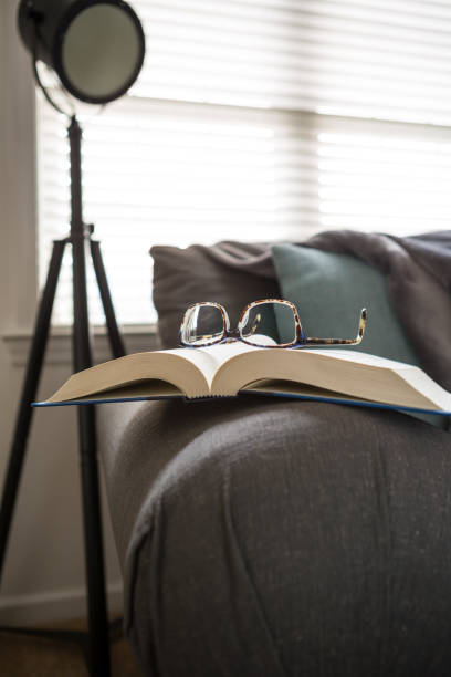 Home concept, Reading at home with book and glasses on sofa in room on a relaxing afternoon stock photo