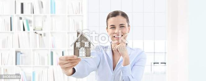 istock home concept smiling woman showing house model, real estate and design 840646814