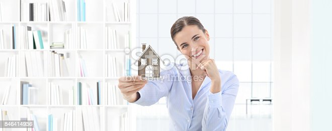 istock home concept smiling woman showing house model, real estate and design 846414936